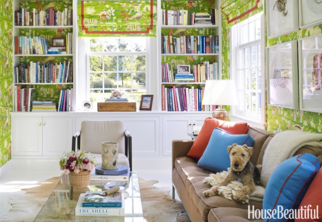 cowhide rug, vibrant green wallcovering and orange pillows in library of Nantucket beach house of Gary McBournie