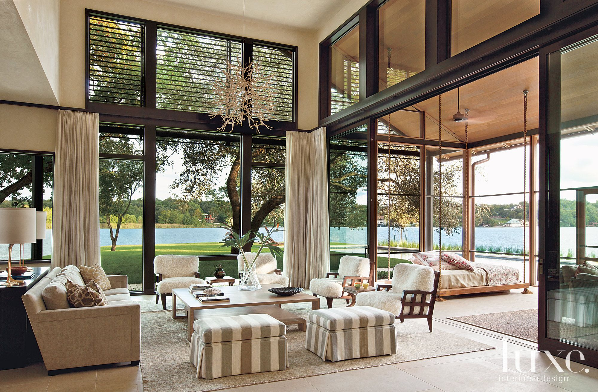 A shaded property in Austin boasting lake views on three sides. This contemporary seating area uses an oversized neutral Oushak rug to seamlessly blend with the room's color palette.