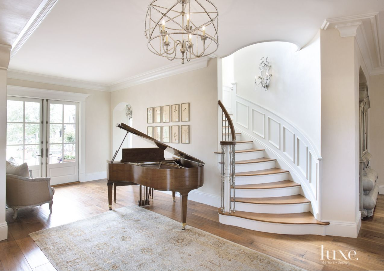 A Scottsdale French countryside home uses an Oushak rug below the focal point, a curved staircase, in this cream entrance hall. This Oushak rug adds depth in this clean, airy space.
