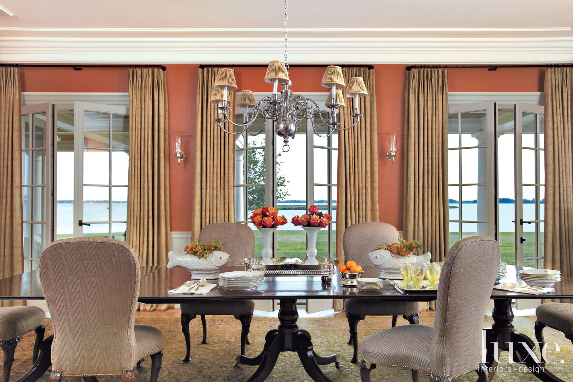 This traditional dining room on a working horse farm overlooks Chesapeake Bay. An oversized Oushak rug reinforces the detail of the golden cream window treatments and chandelier lampshades.