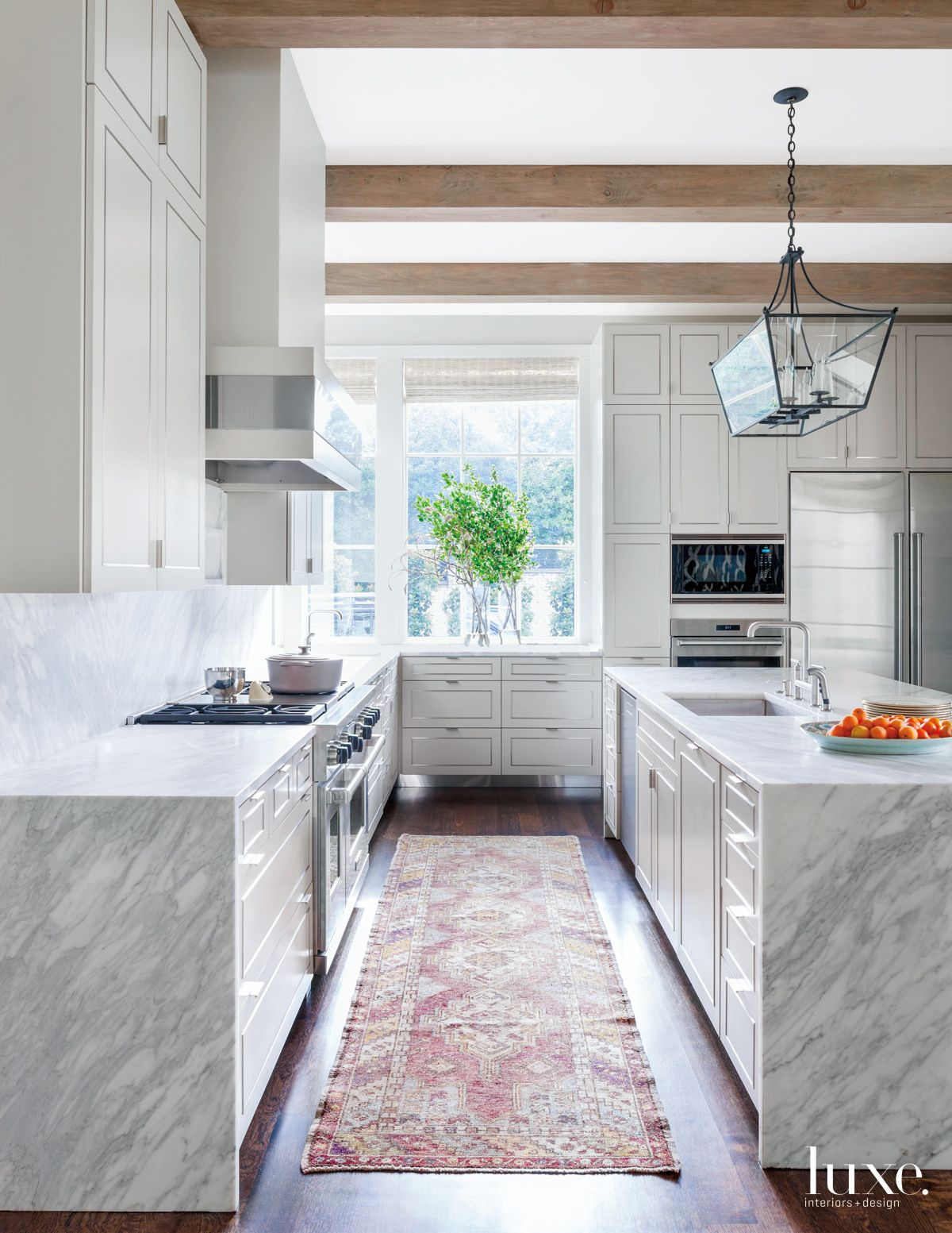 A transitional kitchen has a multi-colored Oushak rug to offset the more modern, white steel-inlaid cabinetry.