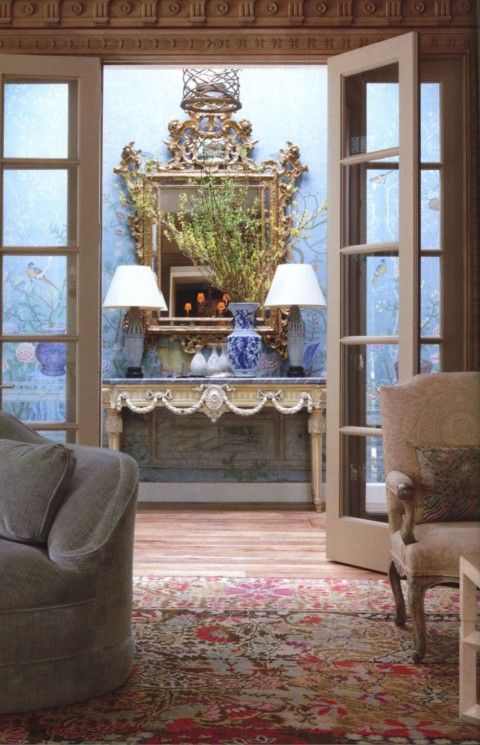 In their living room he used a multi-colored Bessarabian rug that bounces off the pale blue wall covering in the adjoining room.
