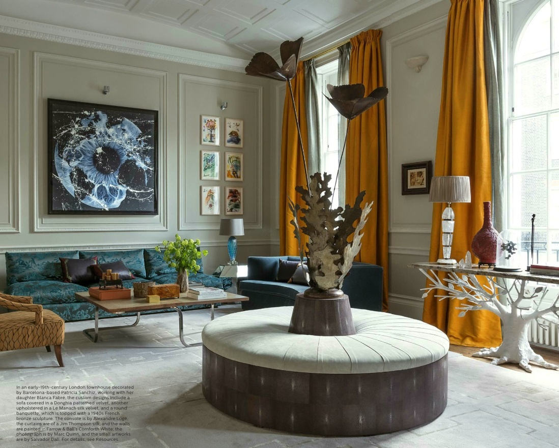 In the same London townhouse, Patricia creates a beautiful atmosphere in the living room. She lets a gray wool and silk geometric rug play second fiddle while the dark-orange drapery, artwork, and bronze statue highlight the room.