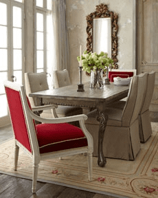 Cream Aubusson and red dining chairs create a modern vibe in this chic dining room