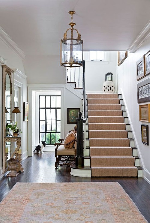 Foyer rug is a blue oushak rug on a dark wood floor in traditional entryway