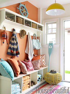 Foyer rug is a orange striped rug in mudroom with orange walls and aqua pillows